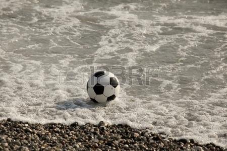 14979199-balon-de-futbol-en-el-agua-en-la-playa.jpg